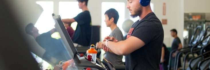 Man checking his watch on a treadmill