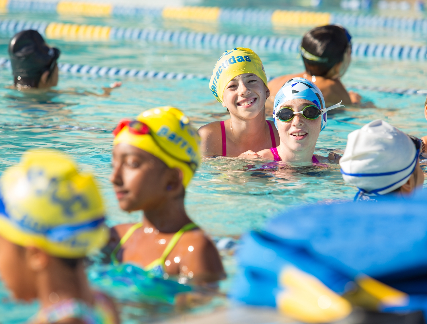 Girls smiling in the PJCC outdoor pool wearing caps and goggles