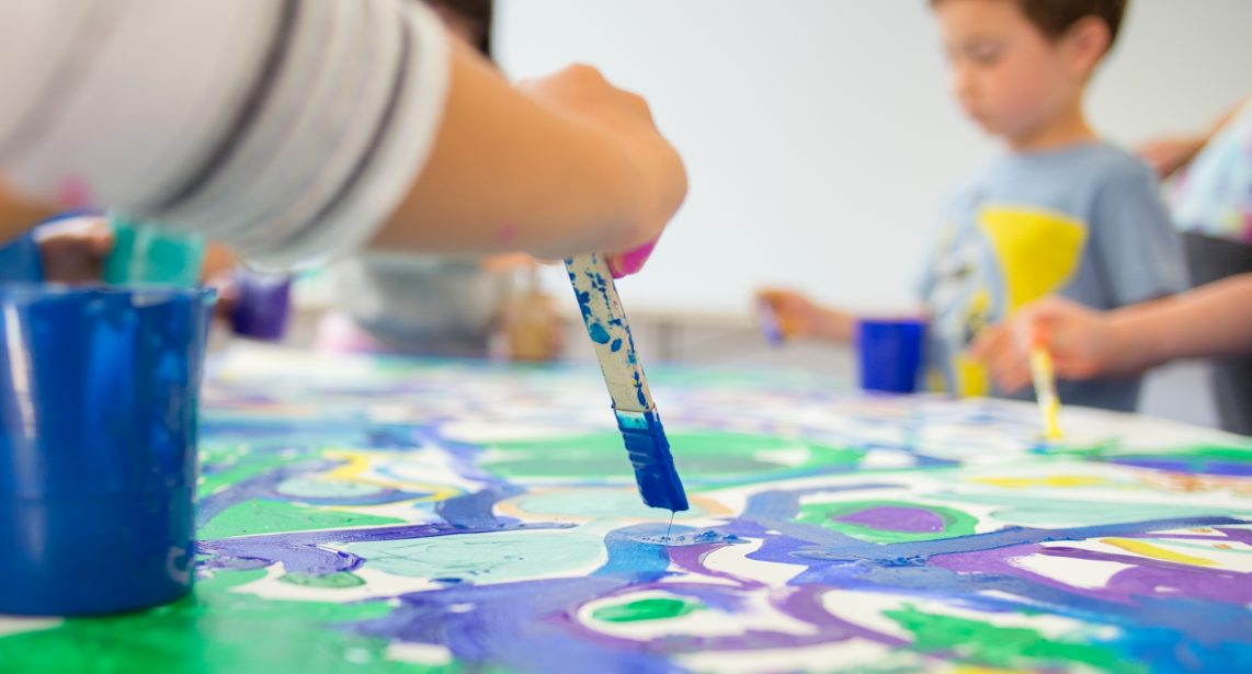 Kids painting a mural in a PJCC classroom