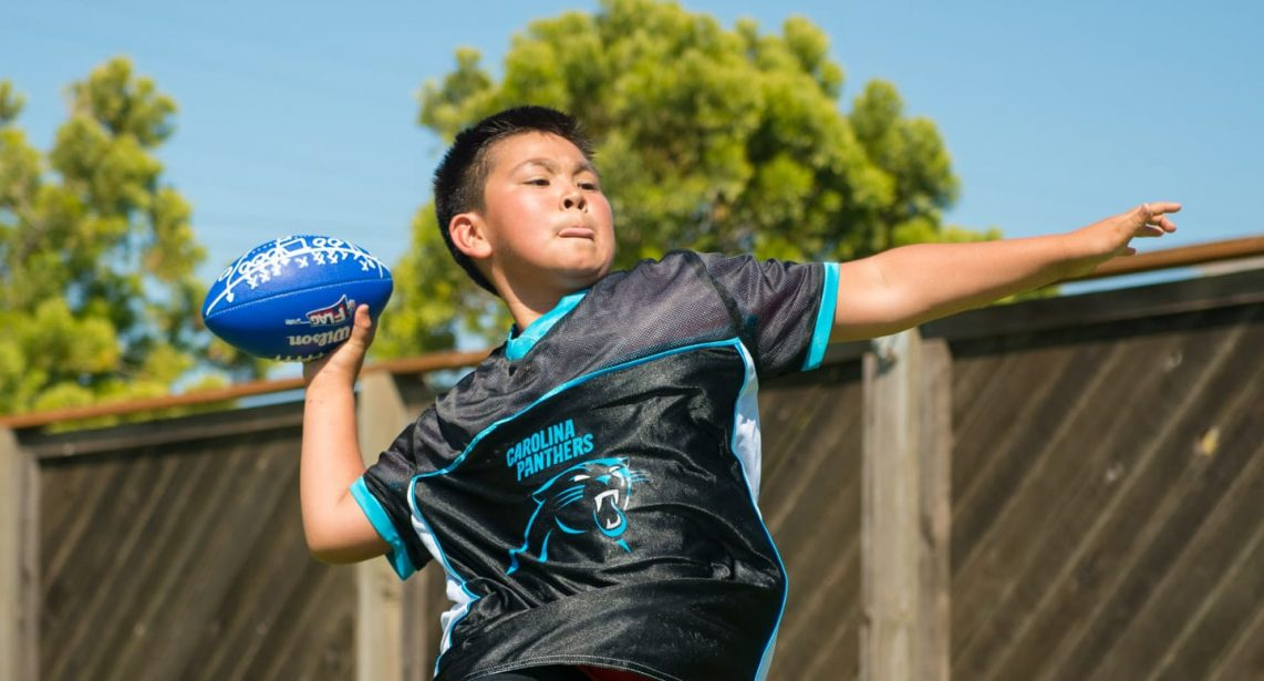 Middle school aged boy throwing a blue football in mid-air outdoors
