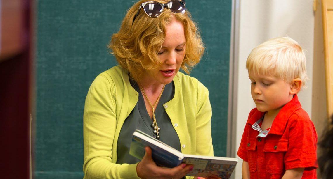 Preschool teacher reading a children's book to a boy