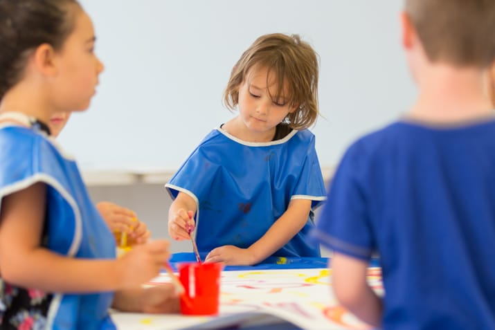 Young children wearing smocks painting a mural in a classroom