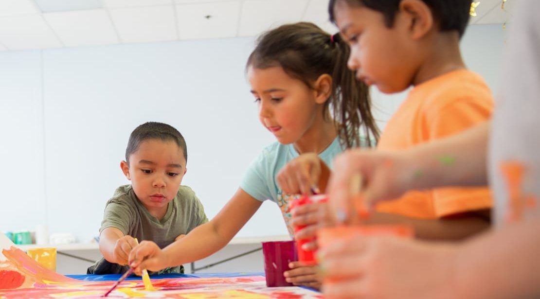 Three young kids painting a mural with orange, pink, and yellow paint