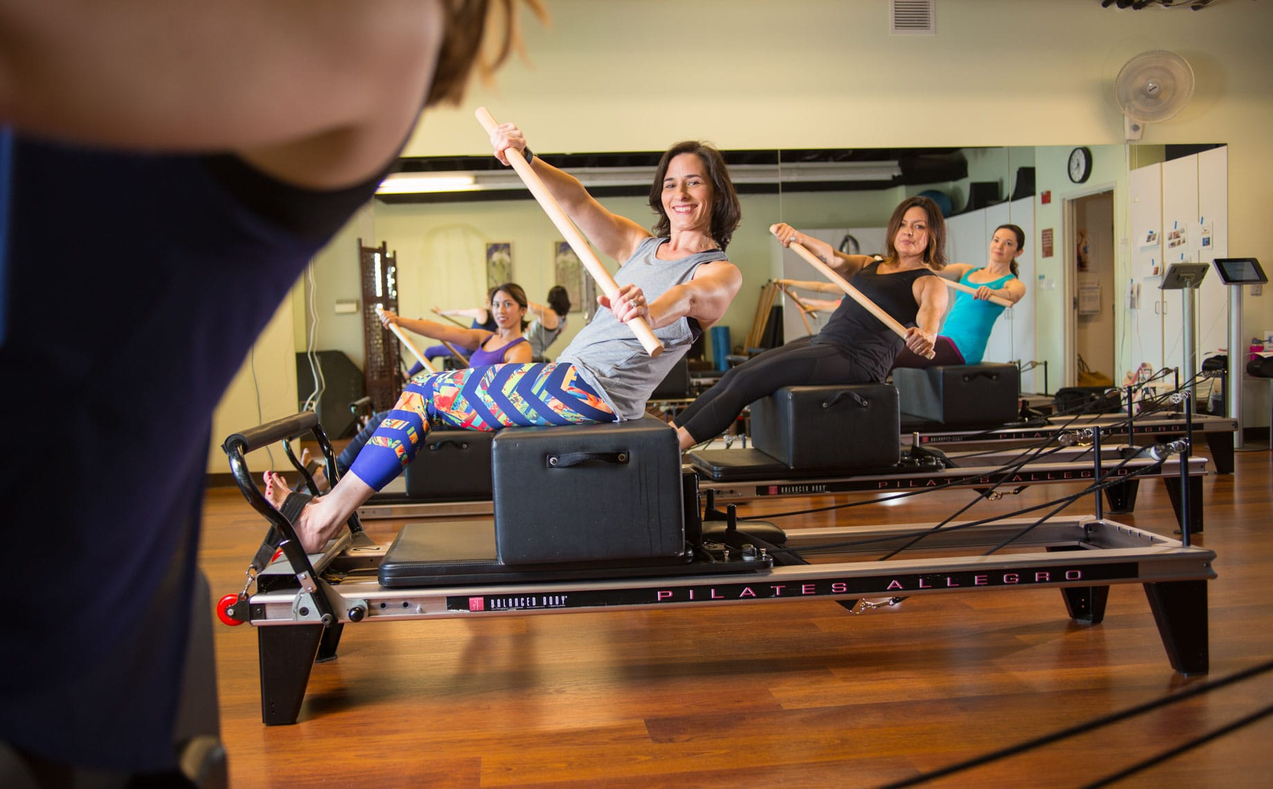 Women in a pilates class on reformers