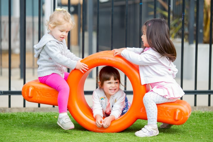 Three young girls on an orange plastic teeter totter