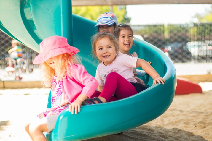 Four young girls on a slide smiling