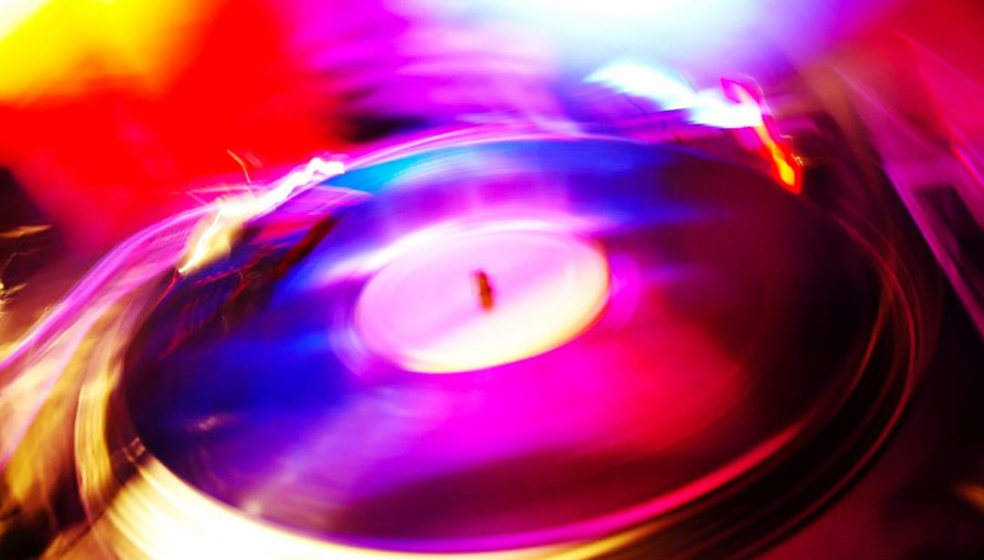 Record player in motion with bright purple, orange, and blue lights