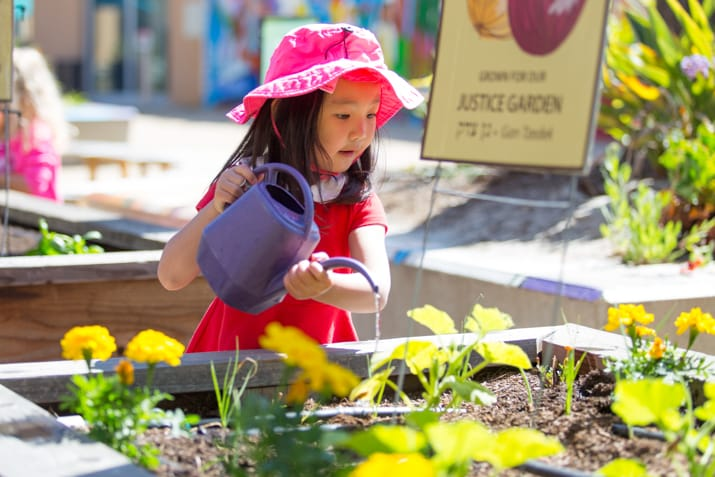 Young girl outside wearing a pink bucket watering the garden