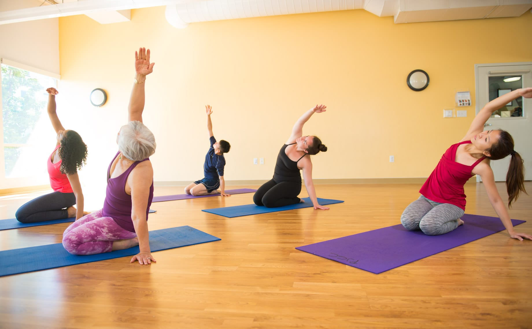 Yoga students stretching on mats at the PJCC yoga studio