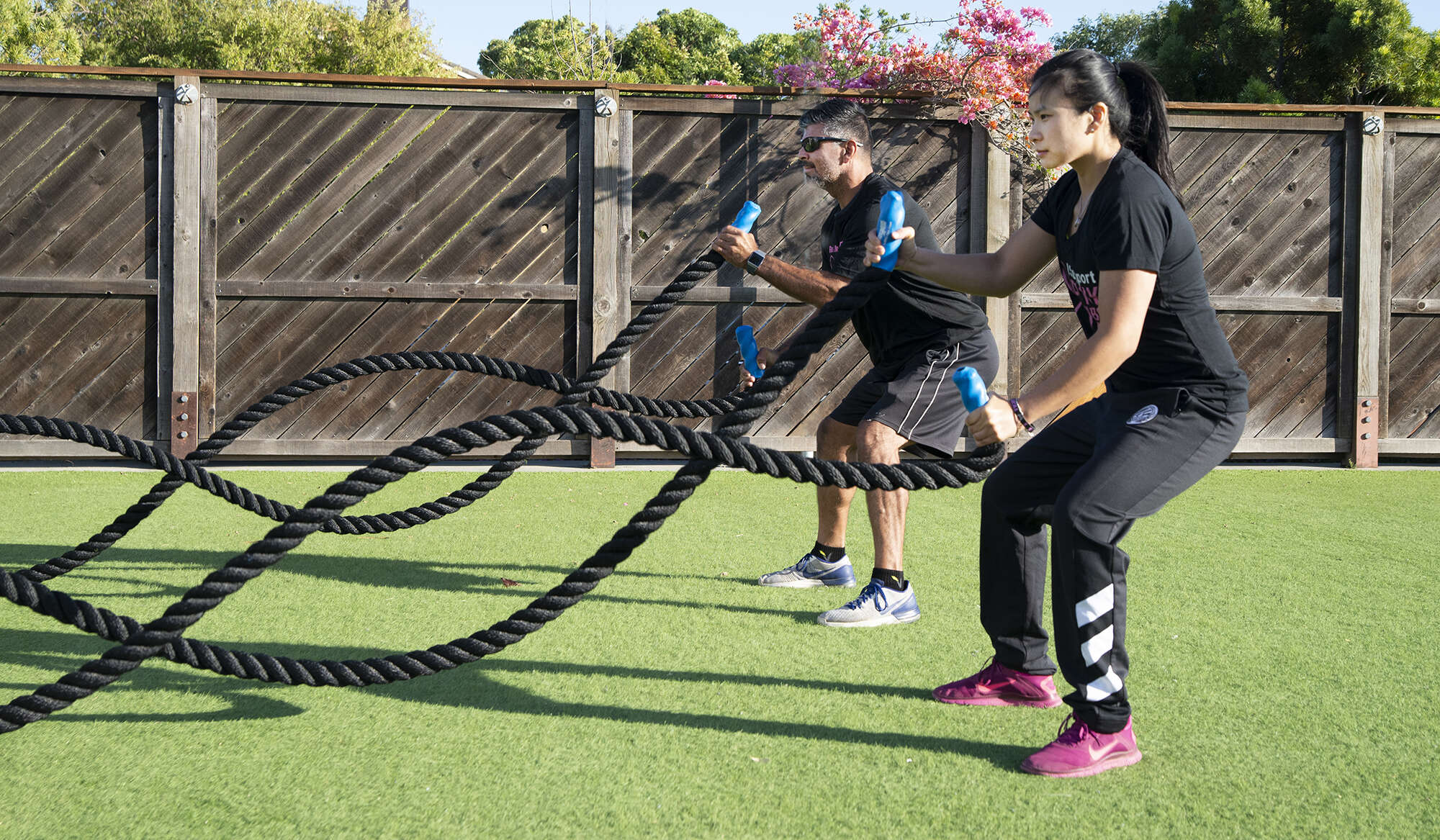 Man and woman tugging rope outdoor exercise class