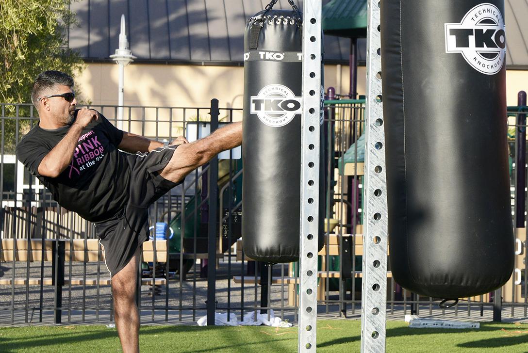 Man kicks exercise bag at gym